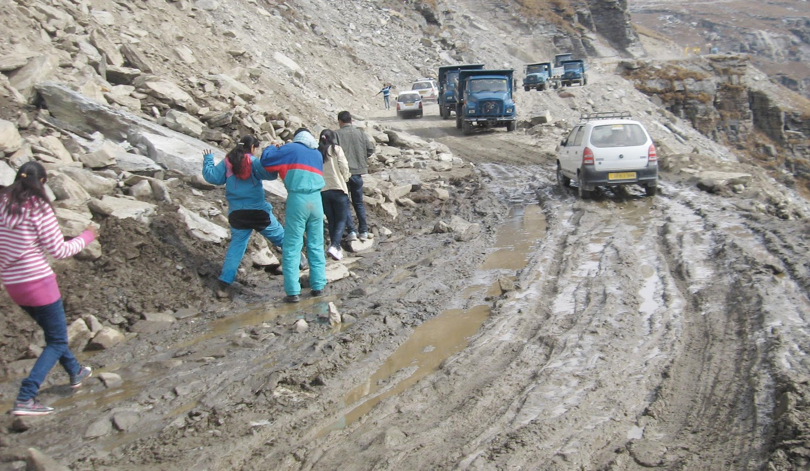 Tourists crossing the slushy road on foot below Rohtang pass